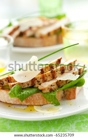 Open chicken Caesar sandwich on the white plate