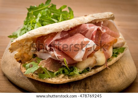 open ciabatta rustic sandwich with green salad grilled chicken breast mozzarella melted cheese and air dry cured Italian ham on wooden board