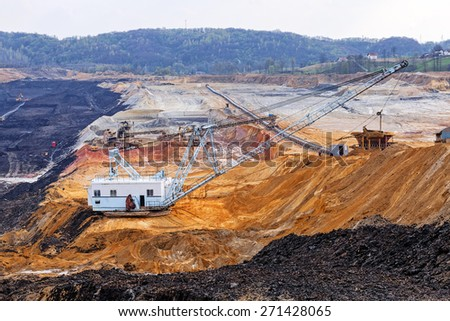 open coal mining pit with heavy machinery - stock photo
