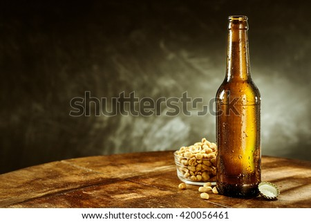 Open cold bottle of beer near a bowl full of peeled oily roasted peanuts on a round rustic wooden table - stock photo