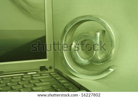 Open computer and arroba in green atmosphere - stock photo