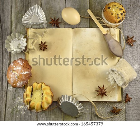 Open cook book with baking goods and kitchen ware on the wooden background - stock photo
