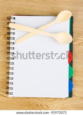 Open cookbook and kitchenware on wooden background - stock photo