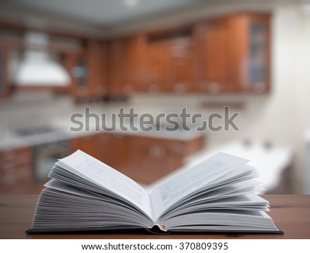 open cookbook on old wooden table in the kitchen