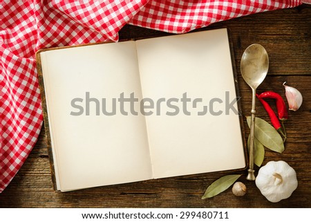 Open cookbook with kitchenware on checkered tablecloth - stock photo