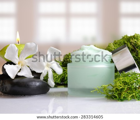 Open cream jar algae. Flowers, black stones and seaweed decoration. Windows background. Front view - stock photo