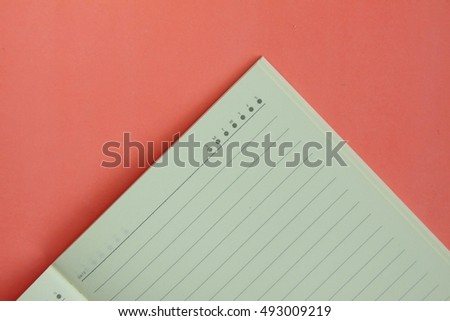 Open daily planner notebook on pink background