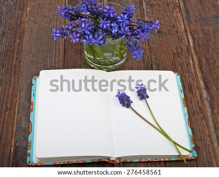Open diary notes on the wooden table and flowers forest hyacinths - stock photo