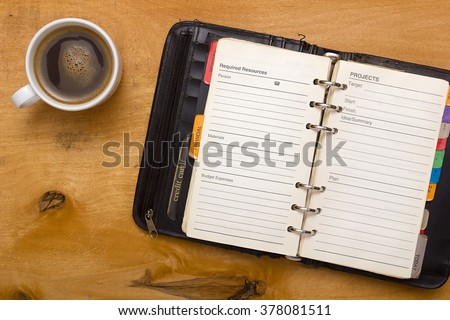 Open diary on wooden table planning their time - stock photo