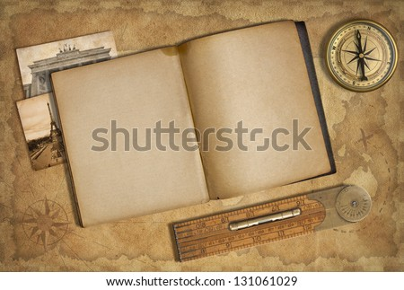 Open diary over old treasure map with compass - stock photo