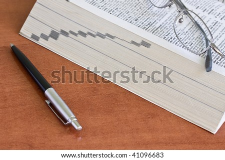 open dictionary with a pair of glasses and pen - stock photo