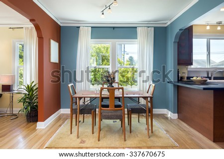Open dining area with blue and red walls in Spanish style home.   - stock photo