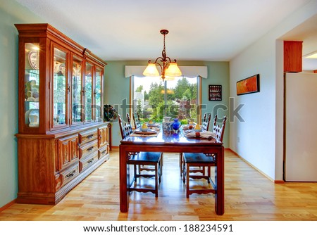 Open dining area with served table and cabinet.