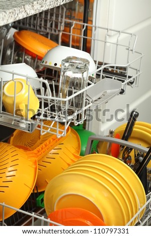 Open dishwasher full of plates, glasses and cutlery - stock photo