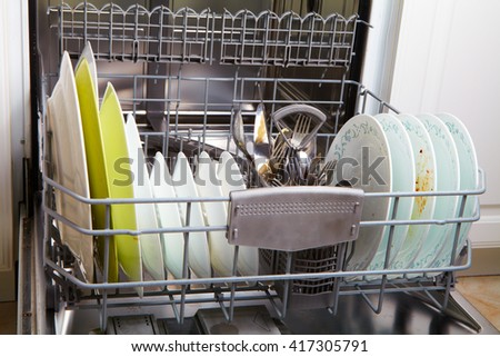 Open dishwasher with clean glass and dishes - stock photo