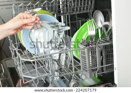 Open dishwasher with clean utensils in it - stock photo