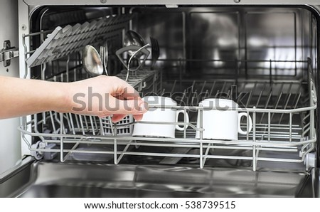 Open dishwasher with clean utensils in it, man hands loading dishes to the dishwasher machine, introducing or taking out a plate and cup, clean tableware after cleaning process