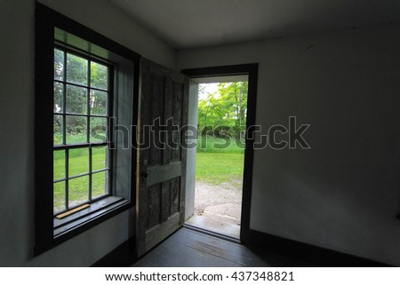 Open Door. Empty room and window with open door leading outside. This is a historical building in a state park and not a privately owned residence. - stock photo