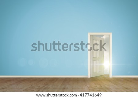 Open door on green wall against blue sky with white clouds - stock photo
