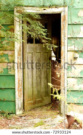 Open door to an abandoned house - stock photo