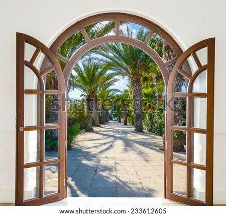 open doorway arch door on the alley of palm trees on a sunny summer day - stock photo