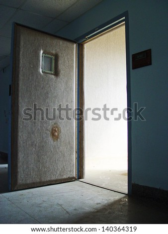 open doorway to a padded room inside an abandoned mental hospital.