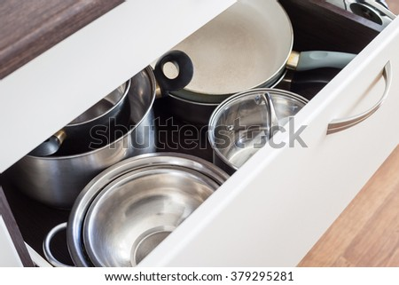 Open drawer of cabinet with steel pots and pans and bowl. Kitchen utensils background - stock photo