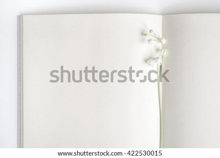 Open empty book with lily of the valley. Blank pages with flower in the middle. - stock photo