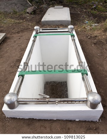 open empty grave with winch to lower casket - stock photo