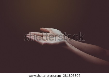 open empty hands with palms up over blurred beautiful bokeh of candle light on sunrise background. Vintage style. Worship, Forgiveness, Mercy, Humble, Evangelical, Thankful, Praise concept. - stock photo