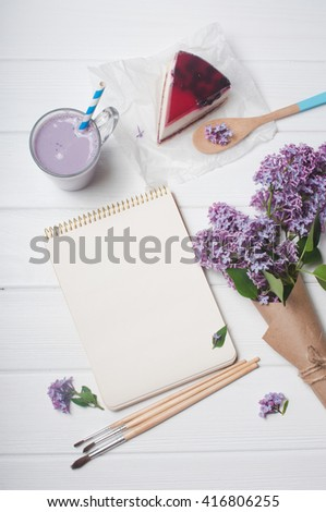Open empty notebook with cup of bilberry milkshake, black current cheesecake slice, brushes and bouquet of lilac flowers in the craft paper on the white wooden background, copy space. Top view. - stock photo