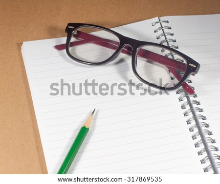 Open empty notebook with green pencil, eyeglasses and lined pages