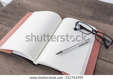 Open empty notebook with pen and glasses,vintage. - stock photo