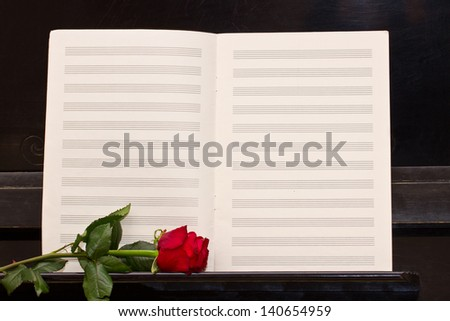 open empty notes paper with one  red rose  piano - stock photo