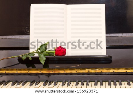 open empty notes paper with red rose on vintage piano - stock photo