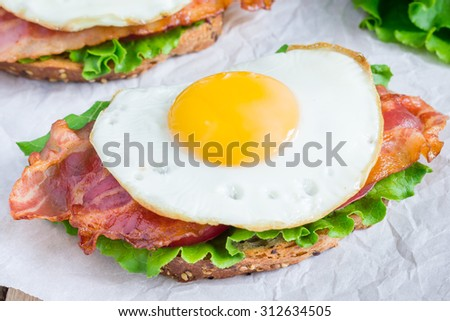 Open face sandwich with egg, bacon, tomato and lettuce - stock photo