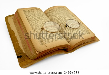 Open faced book with vintage gold-rimmed spectacles - stock photo