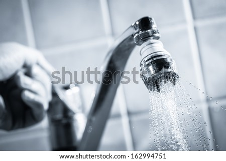 Open faucet and hand, water is running, tinted black and white image