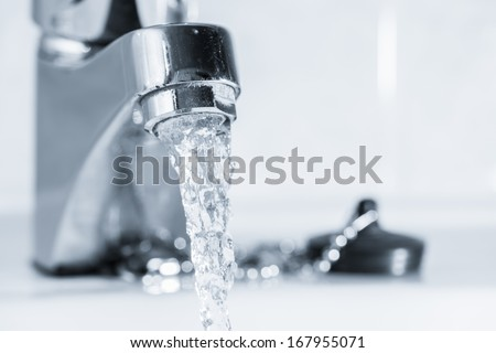 Open faucet in bathroom, water is running, tinted black and white image, horizon format - stock photo