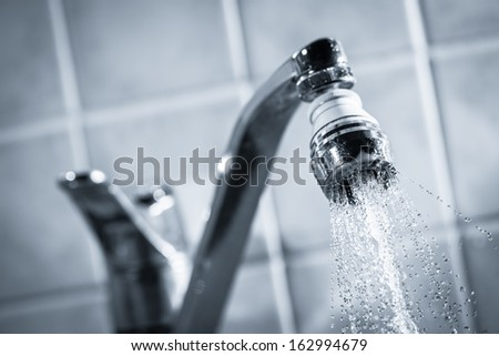 Open faucet, water is running, tinted black and white image
