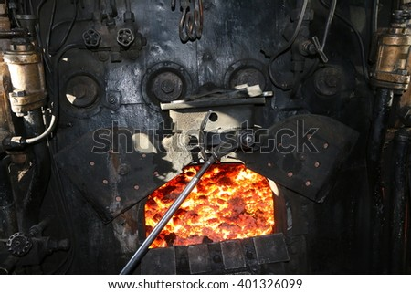 Open fire chamber of a very old steam locomotive with red-hot charcoal