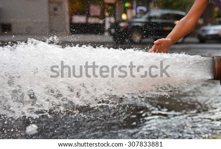 Open fire hydrant/child's hand touching water as it flows vigorously from opened fire hydrant in city street - stock photo