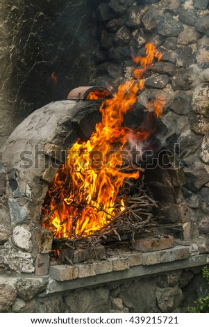 open fire in fire-box of brick fireplace by country cottage - stock photo
