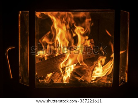 Open fire in oven. Closeup of fireplace with orange fire flame interior. Heating.