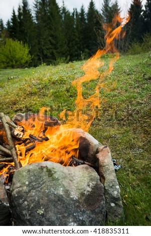 Open fire outdoors. Chic bonfire topped with stones in nature - stock photo