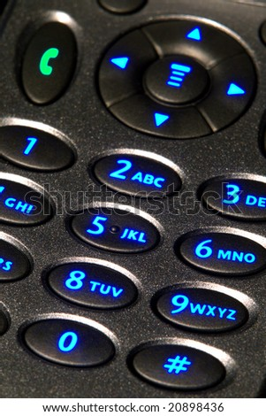 Open flip cell phone with backlit key pad with glowing blue number keys - stock photo