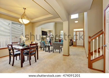 Open floor plan. Dining area and living room with entryway. Creamy tones interior of luxury house. Northwest, USA