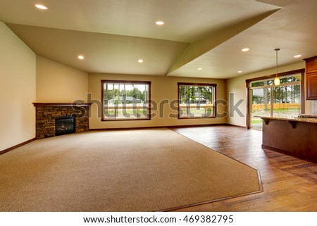 Open floor plan. Empty living room with fireplace, and carpet floor. Connected to kitchen area. Northwest, USA