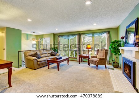 Open floor plan living room interior with green walls, fireplace and leather sofa. Northwest, USA