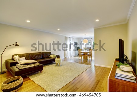 Open floor plan living room interior with leather sofa and carpet. Connected to dining area. Northwest, USA